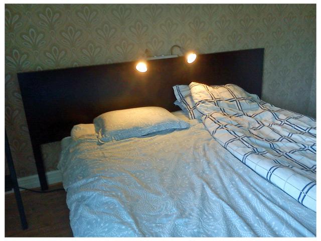 Sänggavel med lampor och säng på plats