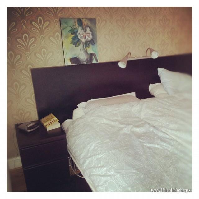 Min sida av sängen, med tavla av Tong Wang på sänggavlen, kvällslektyr och väckarklocka