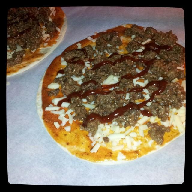 Obakad tortilla pizza med fyllning av pizzasås, riven ost, egen köttfärssås och lite bbq sås från felix överst